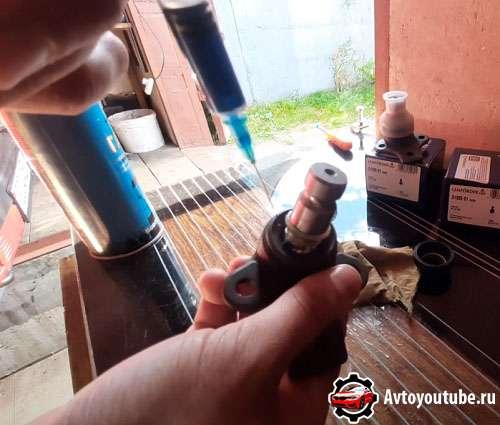 Добавляем шприцем смазку под пыльник шаровой опоры
